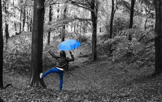 woman dancing in the rain with blue umbrella and blue pants